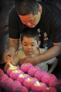 Homme aidant enfant autiste à allumer des bougies