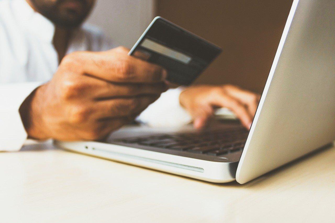 homme tenant une carte bancaire pour effectuer achat en ligne