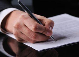 Main tenant un stylo pour écrire sur feuille